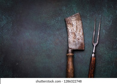 Vintage meat cleaver and fork on grunge concrete background with copy space