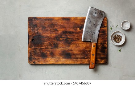 Vintage Meat cleaver on a empty old dark wooden cutting Board. Top view, space for text.