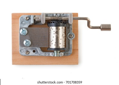 Vintage mechanical music box on a little wooden plank, isolated on white background, top view.
