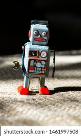 Vintage metal blue robot toy on sunlight. Futuristic concept with small mechanical robot toy walking on cloth surface. Painted eyes and electronic dashboard. Mechanical toy key. Hard light and shadows