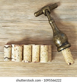Vintage metal corkscrew and corks from wine bottles on a wooden background with copy space. Wine corks close up.