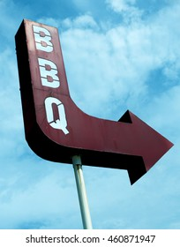 Vintage metal exterior BBQ sign arrow, directing passersby to a rural, country barbecue restaurant