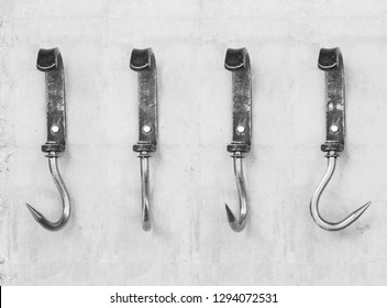 Vintage metal hooks for hay or meat attached to a concrete wall. Isolated view