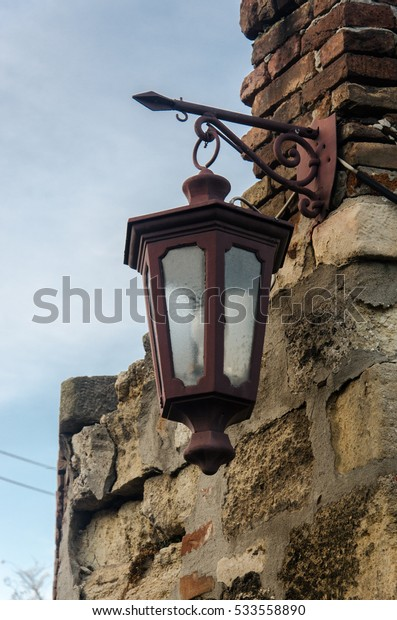 Vintage Metal Lantern on the Old Castle Stone Wall