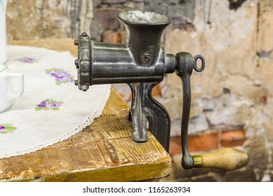 Vintage metal meat grinder attached to a kitchen table.