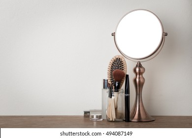 vintage metal mirror and make up set on wooden table.