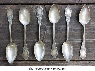 Vintage metal spoons on a wooden table