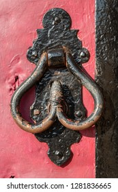 Vintage metallic door handle black on a wooden red painted wooden door background, concept of authentic object, close-up.
