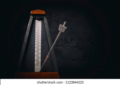 Vintage metronome on dark background. Low key image.