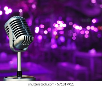 Vintage microphone with blurred night light in restaurant or night club background and soft focus