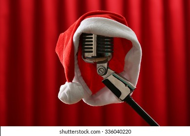 Vintage microphone with Christmas hat on red curtain background