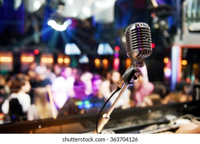Vintage microphone in front of bright color lights inside a disco full of people. Nightlife concept.