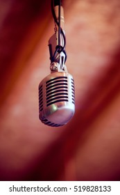 Vintage microphone hanging from above (looking up view).