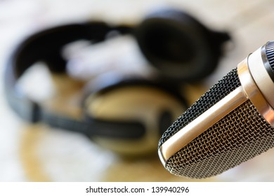 Vintage microphone with headphones in background