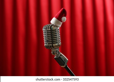 Vintage microphone with little Christmas hat on red curtain background
