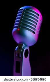Vintage microphone on black with blue and pink highlights