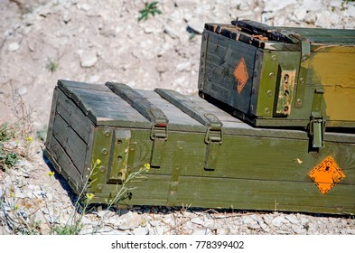 Vintage military suitcase, army box of ammunition in ground. Ammo from Second World War. Soviet army military background of green ammunition on stones. Military ammunition with explosive.
