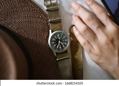 Vintage military wristwatch with nato leather strap and brown straw hat. Classic timepiece mechanical watch, Men fashion and accessories.