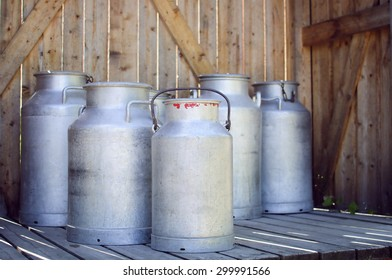 Vintage milk cans on wooden background