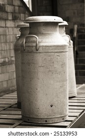 vintage milk churns photographed in black and white