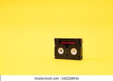 Vintage mini DV cassette tape used for recording video back in a day. Plastic, magnetic, analog film tape on yellow background
