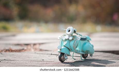 vintage miniature toy motorbike in sunny autumn park