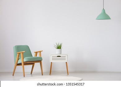 Vintage mint armchair next to small white table with green plant in pot in bright interior, real photo with copy space on the empty wall