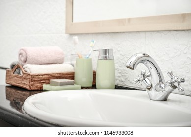 Vintage mixer tap in the bathroom with liquid soap dispenser, tooth brushes and towels closeup
