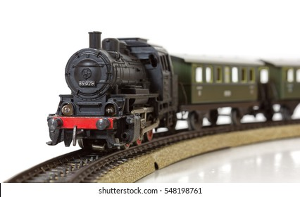 Vintage model electric train formed by a steam locomotive and green passenger cars on the rails