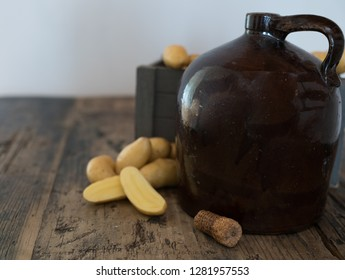 vintage moonshine jug on a rustic wooden table with potatoes and corn cob cork for distilling hard liquor