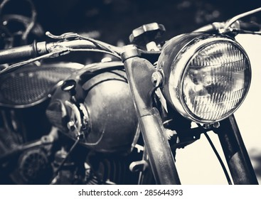 Vintage motorbike, focus on a headlamp. Retro motorcycle with headlight on black and white colors.