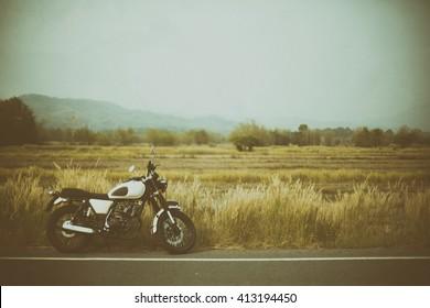 Vintage-Motorrad auf einer schönen Route im Grunge-Stil