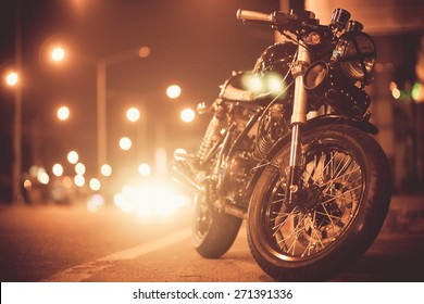 Vintage motorcycle on  road at night towards city