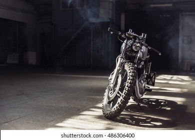 Vintage motorcycle standing in a dark building in the rays of sunlight. Toned colors. Front view