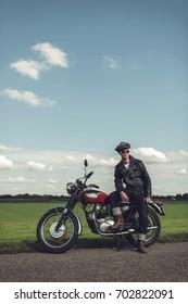 Vintage motorcyclist having a break along rural road in summer.