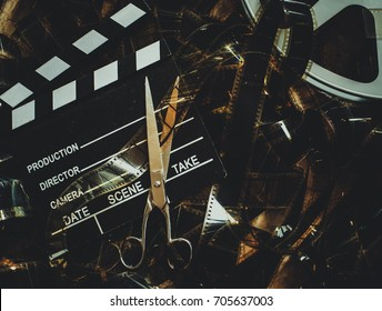 Vintage movie background in cinematic color effect, unrolled 35mm filmstrip clapper board and scissors concept of editing final cut