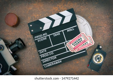 Vintage movie camera, movie in a metal box, clapperboard, light meter and two movie tickets