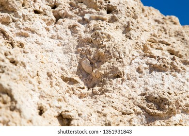 Vintage mud wall in the desert made with beach rocks and coral stones. Natural background.