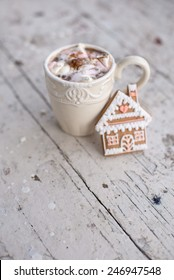 Vintage mug of Cocoa with marshmallows hot drink with gingerbread cookie and cinnamon sticks and anise stars on a white shabby table