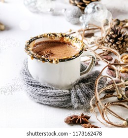 Vintage mug in wool scarf of hot chocolate, decor with nuts, caramel, spices. Ingredients and Christmas toys above over white texture background with space. Square image