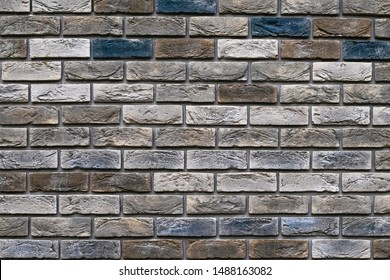 Vintage multi-colored bricks background, grunge texture. Old weathered brick wall. Decorative tile surface. Rough brickwork.