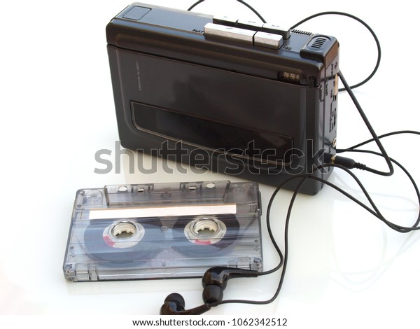 vintage music cassette tape and walkman recorder over white white background