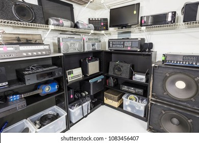 Vintage music and electronics store set with shelves full of equipment.