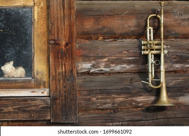 A vintage musical trumpet hangs from a rusty nail on the sturdy brown wood wall of the Forester's Lodge.A strong century-old log house with a funny children's toy piggy Bank in a small window.Russia
