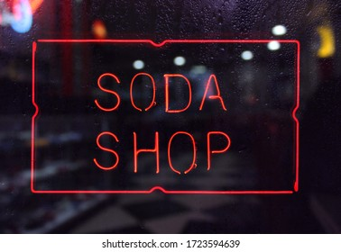 Vintage Neon Soda Shop Sign in Rainy Window