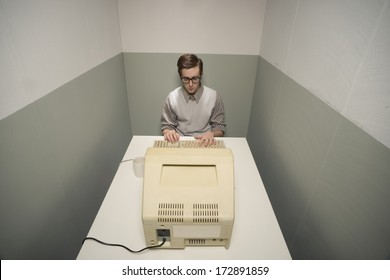Vintage nerd guy working on old computer in a small room.