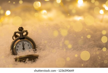Vintage New year clock and cones covered with snow.