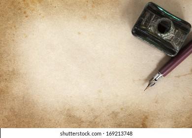 Vintage nib pen and inkwell, over grunge paper.