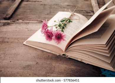 Vintage novel books with bouquet of flowers on old wood background - concept of nostalgic and remembrance in spring vintage background