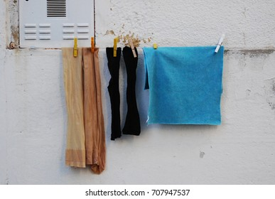 Vintage nylons, black stockings and a blue dishtowel hanging on a line in front of grey Cuban wall